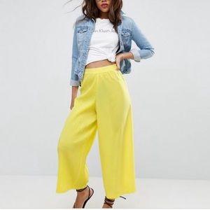 Neon yellow wide leg cropped pants.